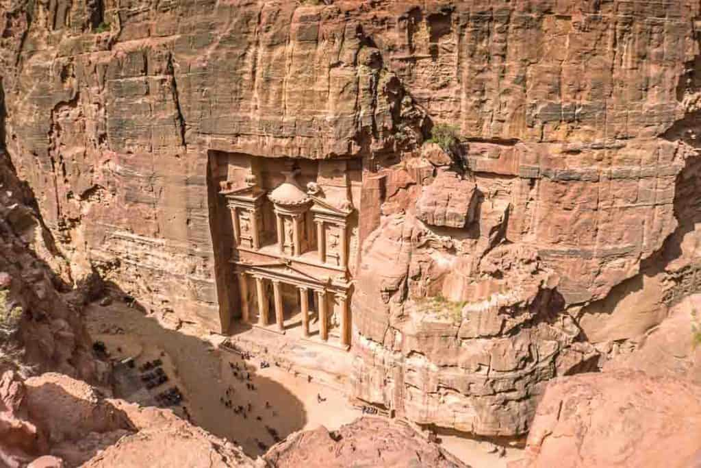 This photo taken inside Petra by Ketki R S. shows the Treasury at Petra as seen from above by hiking the Treasury Overlook Trail (Al-Khubtha Trail) stairs. The photo appears on Petra Travel guide post on the travel blog, Dotted Globe.
