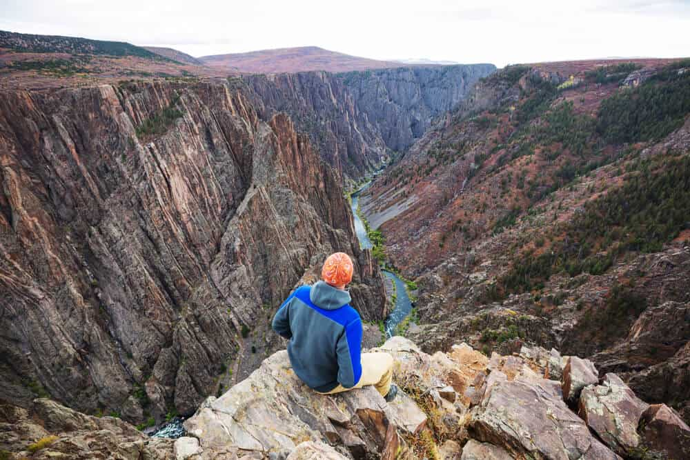 A tourist gazing at the Granite Cliffs of the Black Canyon
